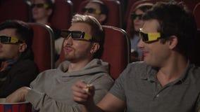 Vänner som äter popcorn i filmbiograf Hållande ögonen på film för folk i exponeringsglas 3d stock video