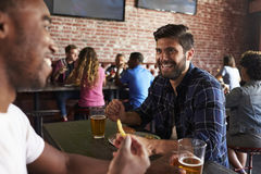 Vänner som äter ut i sportstång med skärmar i bakgrund arkivfoto