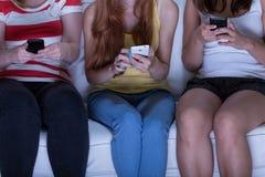 Vänner som överför textmeddelanden Fotografering för Bildbyråer