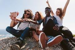 Vänner som överst sitter av ett berg som tar selfie royaltyfri fotografi