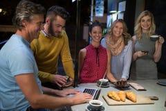 Vänner som använder elektroniska grejer, medan ha kaffe Arkivfoton
