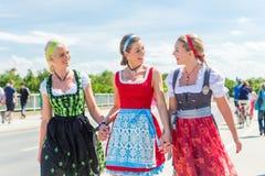 Vänner som besöker den bayerska mässan som har gyckel Fotografering för Bildbyråer