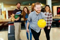 Vänner som bowlar på klubban Royaltyfri Foto