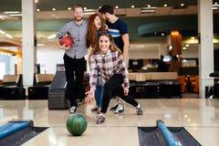 Vänner som bowlar på klubban Arkivbild