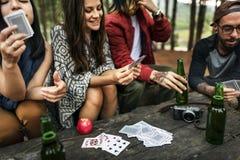 Vänner som campar spela kortbegrepp royaltyfri fotografi