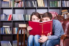 Vänner som döljer bak en bok som ser sig Royaltyfria Bilder