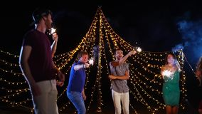 Vänner som dansar med tomtebloss under nattstrandpartiet stock video