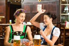 Vänner som dricker öl i den bayerska baren som spelar kort Royaltyfria Bilder