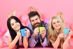 Vänner som dricker kaffe i säng Man och kvinnor i inhemsk kläder, pyjamas Man och kvinnor, vänner på lekmanna- lyckliga framsidor Royaltyfri Bild