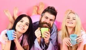 Vänner som dricker kaffe i säng Mannen och kvinnor, vänner på att le framsidor lägger, rosa bakgrund Man och kvinnor i hemhjälp Royaltyfri Foto