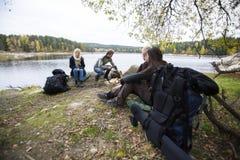 Vänner som förbereder sig för att campa för Lakeside royaltyfri fotografi