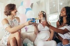 Vänner som firar baby shower med fruktsafter Arkivfoton