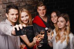 Vänner som firar jul som gör selfie fotografering för bildbyråer