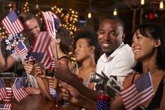 Vänner som firar Juli 4th på ett parti i en stång Royaltyfria Bilder