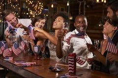 Vänner som firar Juli 4th på ett parti i en stång Arkivfoton