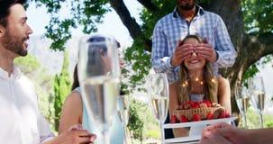Vänner som firar kvinnas födelsedag på den utomhus- restaurangen arkivfilmer
