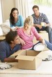 Vänner som flyttar sig in i det nya hemmet som packar upp askar Royaltyfri Bild
