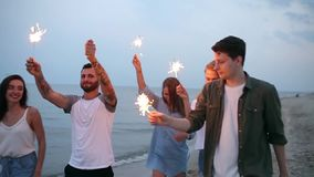 Vänner som går, dansar och har gyckel under nattpartiet på sjösidan med det bengal tomteblosset, tänder i deras händer stock video