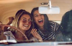 Vänner som går på semester i en bil och har gyckel royaltyfri bild