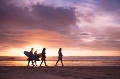 Vänner som går på stranden i aftonen royaltyfri foto