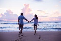 Vänner som går på stranden på solnedgången på semester Royaltyfria Foton