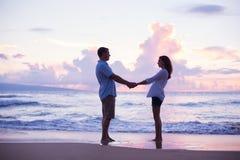Vänner som går på stranden på solnedgången på semester Royaltyfri Bild