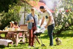 Vänner som gör grillfesten att grilla på sommarpartiet arkivfoton