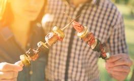 Vänner som gör grillfesten och har lunch i naturen Koppla ihop att ha gyckel, medan äta och dricka på en lycklig pic-nic - arkivfoto