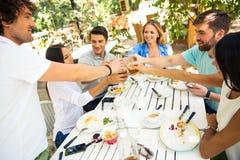 Vänner som gör rostat bröd runt om tabellen Royaltyfria Foton