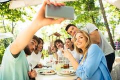 Vänner som gör selfiefotoet i utomhus- restaurang