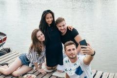 Vänner som gör selfiesammanträde på pir med sjöbakgrund medan royaltyfria foton