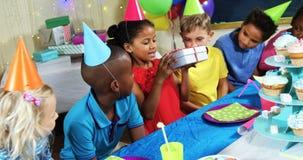 Vänner som ger gåvaasken till flickan under födelsedagpartiet 4k lager videofilmer