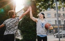 Vänner som ger höjdpunkt fem efter en lek av streetball Royaltyfri Fotografi
