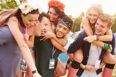 Vänner som ger ridturer på axlarna till och med campingplats för musikfestival royaltyfri fotografi