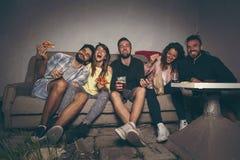 Vänner som håller ögonen på en film på ett byggande tak arkivfoton
