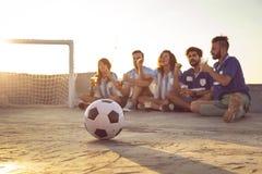 Vänner som håller ögonen på en fotbollsmatch royaltyfri bild
