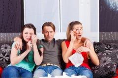 Vänner som håller ögonen på en ledsen film i TV Royaltyfri Foto