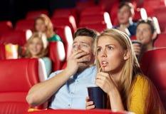 Vänner som håller ögonen på fasafilm i teater Arkivbilder