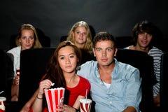 Vänner som håller ögonen på film på bion Royaltyfri Fotografi