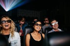 Vänner som håller ögonen på filmen 3d, i teater och att skratta Royaltyfri Fotografi