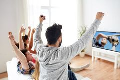 Vänner som håller ögonen på fotboll- eller fotbollleken på tv royaltyfria bilder