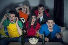 Vänner som håller ögonen på fotbollleken på TV arkivbild