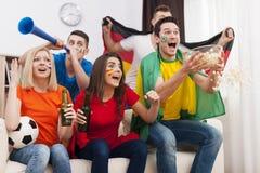 Vänner som håller ögonen på fotbollleken på TV arkivbilder