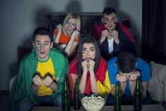 Vänner som håller ögonen på fotbollleken på TV Royaltyfri Foto