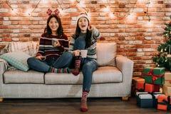 Vänner som håller ögonen på komedi som är hemmastadd på julhelgdagsafton fotografering för bildbyråer