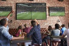 Vänner som håller ögonen på leken i sportstång på att fira för skärmar royaltyfri fotografi