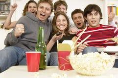 Vänner som håller ögonen på television och att hurra Royaltyfri Bild