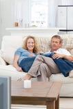 Vänner som håller ögonen på tv:n i vardagsrumet Royaltyfria Bilder
