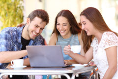 Vänner som håller ögonen på video i en bärbar dator i en coffee shop Royaltyfri Fotografi