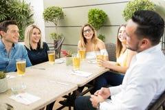 Vänner som har bra tid i en restaurang royaltyfria bilder